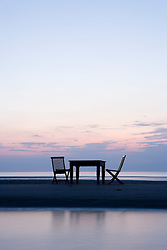 Table and chairs on a beach at dawn Massachusetts USA
