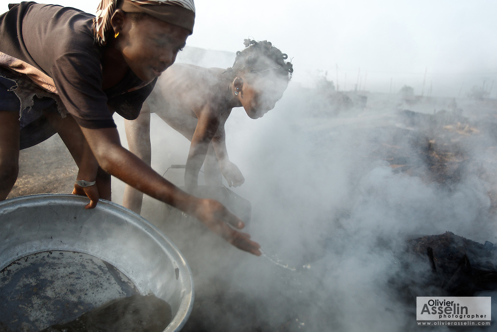 Girls splash water on hot charcoal at a wood charcoal production site on the outskirts of San Pedro, Bas-Sassandra region, Côte d'Ivoire on Sunday March 4, 2012. Men, women and children - who don't go to school - work here seven days a week.