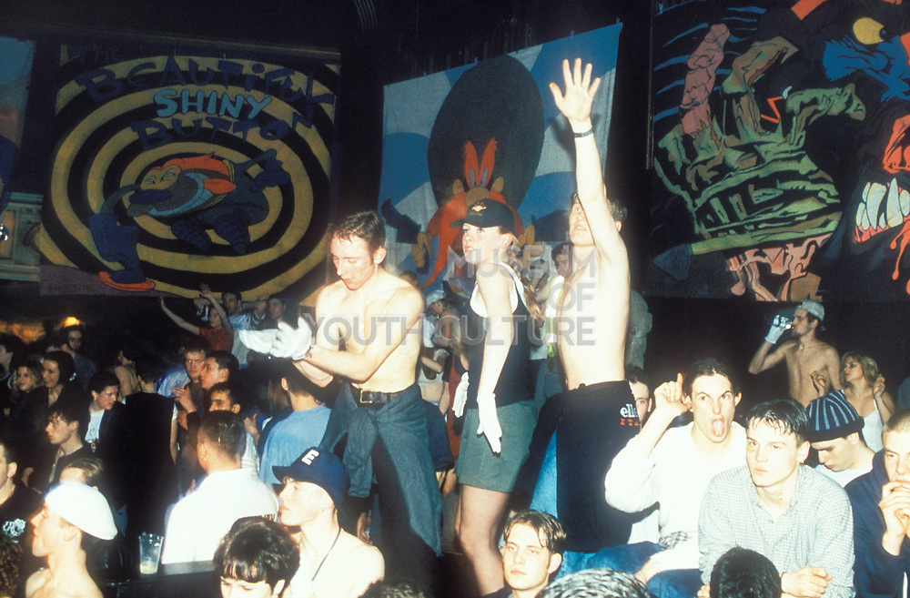 Topless men on crowded dancefloor in hardcore rave, U.K, 1990s.