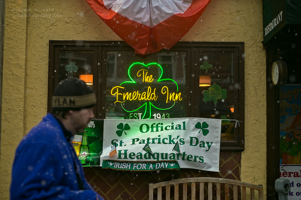 Man walking past Irish bar in snow on day before St. Patrick's Day.