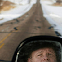 "Former Medina, N.D. police chief Darrell Graf reflects in the rearview mirror of his vehicle as he looks at the road where the Gordon Kahl shootout occurred 25 years ago on Feb. 13, 1983, on Stutsman County Road 68 just north of Medina, N.D. Darrell is still held prisoner by 30 seconds of gunfire and the aftermath that followed. Graf didn't fire a shot, but he was there just the same. Memories from the shootout and the reaction and treatment Graf says he received afterward have destroyed his life. In an effort to get out his story, the 52-year-old Graf, who no longer works in law enforcement, wrote a book, ""It's All About Power,"" and is dedicated to victims of post-traumatic stress disorder and includes Graf's own descriptions of his struggle since the shootout."