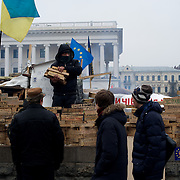 December 20, 2013 - Kiev, Ukraine: A pro-EU demonstrator builds a wall with wooden bricks printed with the names of every village and city who's population have representation in the month long protests at the Independence Square, also know as Maidan, in central Kiev.<br /> On the night of 21 November 2013, a wave of demonstrations and civil unrest began in Ukraine, when spontaneous protests erupted in the capital of Kiev as a response to the government&rsquo;s suspension of the preparations for signing an association and free trade agreement with the European Union. Anti-government protesters occupied Independence Square, also known as Maidan, demanding the resignation of President Viktor Yanukovych and accusing him of refusing the planned trade and political pact with the EU in favor of closer ties with Russia.<br /> After a days of demonstrations, an increasing number of people joined the protests. As a responses to a police crackdown on November 30, half a million people took the square. The protests are ongoing despite a heavy police presence in the city, regular sub-zero temperatures, and snow. (Paulo Nunes dos Santos/Polaris)