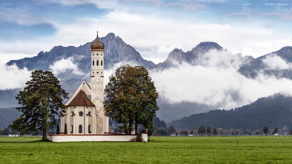 Eine Kirche mit Postkartenidylle ist die Wallfahrtskirche St. Coloman auf dem freien Feld in Schwangau. Die barocke Wallfahrtskirche liegt malerisch zwischen Wiesen und Feldern vor der vor dem imposanten Panorama der Allgäuer Berge und in unmittelbarer Nähe der Königsschlösser Neuschwanstein und Hohenschwangau und ist ein beliebtes Fotomotiv auf Postkarten.