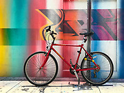 Red bicycle parked in front of a mural in Miami's Wynwood Arts District