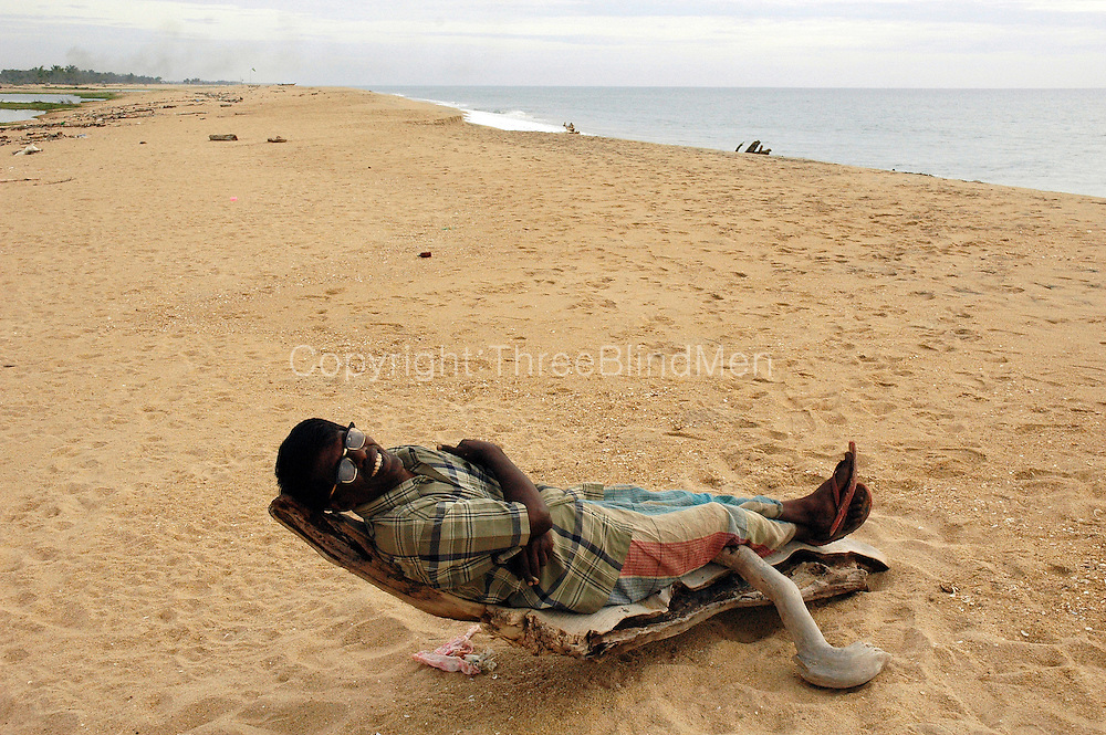 Tsunami. Mr. Nazeer, who lost his wife and many children in the tsunami relaxes on a piece of driftwood on the beach at Akbar Town, Kalmunai.