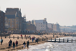 Portobello, Scotland, UK. 25 April 2020. Views of people outdoors on Saturday afternoon on the beach and promenade at Portobello, Edinburgh. Good weather has brought more people outdoors walking and cycling. The beach appears busy with possibly a breakdown in social distancing happening later in the afternoon. View along beach showing large number of people.  Iain Masterton/Alamy Live News