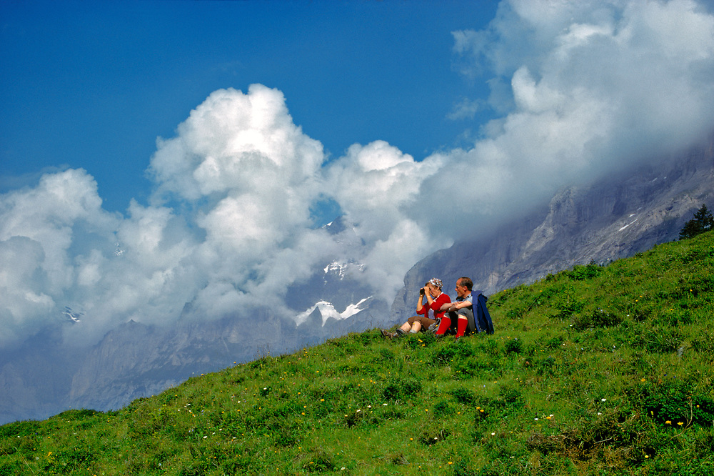 Hikers take a rest along a trail in the Berner Oberland in Switzerland.