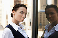 Woman standing outdoors reflected in window head and shoulders