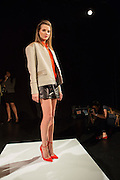 Black shorts, a bright tangerine collared blouse, and a long-sleeved jacket, with orange high-heeled pumps. By Monika Chiang at Spring 2013 Fashion Week in New York.