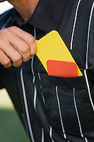 Referee taking card from pocket mid section