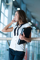 Businesswoman on mobile phone holding folder