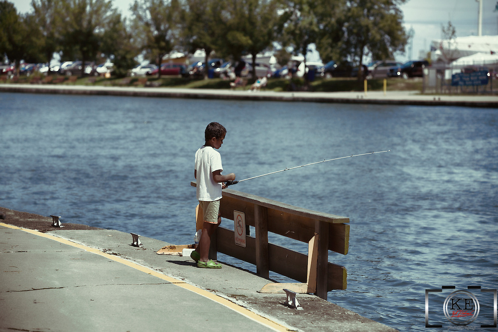A young boy fishing in a canal.