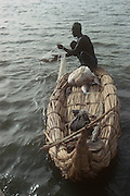 Africa, Sahel region, Chad, Islands of Lake Chad. Kanembu fisherman in papyrus reed canoe removing fish from nylon net. Nylon nets were introduced in the 1950s.