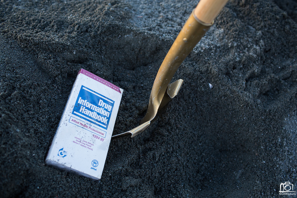 A text book and gold painted shovel sit in the dirt during the Milpitas Unified School District and San Jose Evergreen Community College District Community College Extension Ground Breaking Ceremony near Russell Middle School in Milpitas, California, on November 17, 2015. (Stan Olszewski/SOSKIphoto)