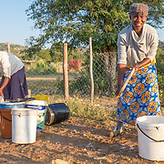 CAPTION: Claudia and Bambanani wash the buckets they use for collecting water near an old pump. More borehole pumps mean more people like them will have easier access to water for household use, as well as for agriculture. LOCATION: Mawoneke Village, Chivi District, Masvingo Province, Zimbabwe. INDIVIDUAL(S) PHOTOGRAPHED: Claudia Masasire (left) and Bambanani Maphosa (right).