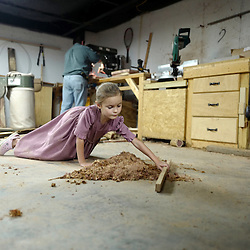 6 year-old Staci Kauffman plays with sawdust as her father Martin Kauffman, a Mennonite makes a wooded stool in his basement. Kauffman who after work at the 5-Star Buildings spends his spare time making furniture at his home in Leasburg, Missouri on Tuesday, Sept. 27, 2016. (Photo by Keith Birmingham Photography)
