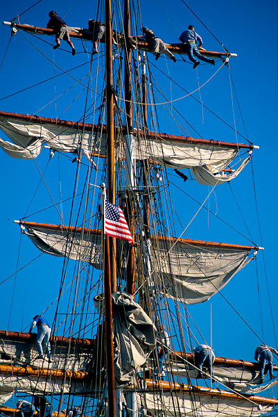 Men climbing the masts and rigging the sails on a sailboat in Galveston Texas