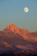 At sunset, a nearly full moon rises over Mt. Clark in Yosemite National Park, California.