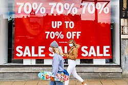 Edinburgh, Scotland, UK. 28 July, 2020. Business and tourism slowly returning to the shops and streets of Edinburgh city centre. Women walk past shop window of Topshop on Princes Street with large sale poster on display. Iain Masterton/Alamy Live News