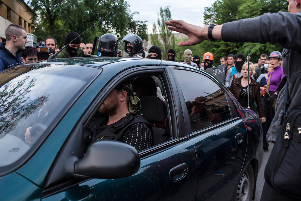 DONETSK, UKRAINE - MAY 4: Pro-Russian protesters drive away with a man who was beaten, detained, and accused of being a provocateur outside the Executive Council building on May 4, 2014 in Donetsk, Ukraine. Cities across Eastern Ukraine have been overtaken by pro-Russian protesters in recent weeks, leading the Ukrainian military to respond with force in some areas. (Photo by Brendan Hoffman for The Washington Post)
