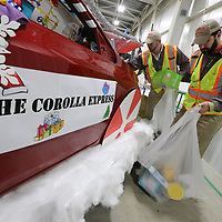 Nathan Ratliff, left, and David Martin begin removing toys that were donatted and filled an empty Toyota Corolla as part of the Toyota team helping the Salvation Army Angel Treet.