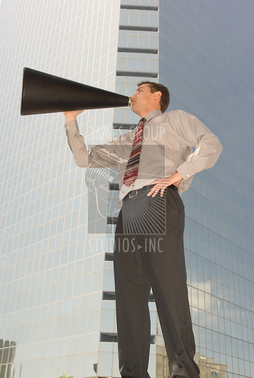 Worm's eye view of a businessman holding a megaphone with a skyscraper in the background