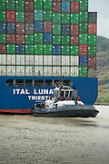 Containers cargo ship and tugboat near Miraflores Locks. Panama Canal, Panama City, Panama, Central America.
