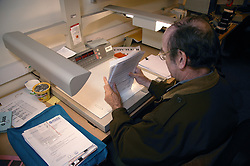 Man with disability working as microfilm technician; sitting at desk in visual communications office organising papers,
