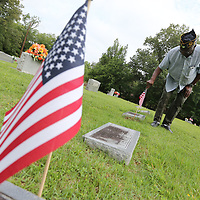 Clarence Partlow puts down another flag marking the grave of veteran at Plantersville Cemetery Tuesday as the local chapter of the American Legion  gets ready for Memorial Day.