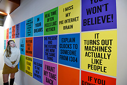 """© Licensed to London News Pictures. 27/10/2019. LONDON, UK. A staff member poses next to """"Slogans for the 21st Century"""", 2011 - ongoing, by Douglas Coupland.  Advance preview of """"24/7: A Wake-Up Call For Our Non-Stop World"""", a new exhibition opening on 31 October at Somerset House.  The show examines our inability to switch off from our 24/7 culture.  Over 50 multi-disciplinary works explore the pressure to produce and consume information around the clock. taking visitors on a 24-hour cycle from dawn to dusk through interactive installations.  Photo credit: Stephen Chung/LNP"""