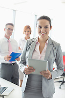 Portrait of happy businesswoman holding digital tablet with colleagues in background at office