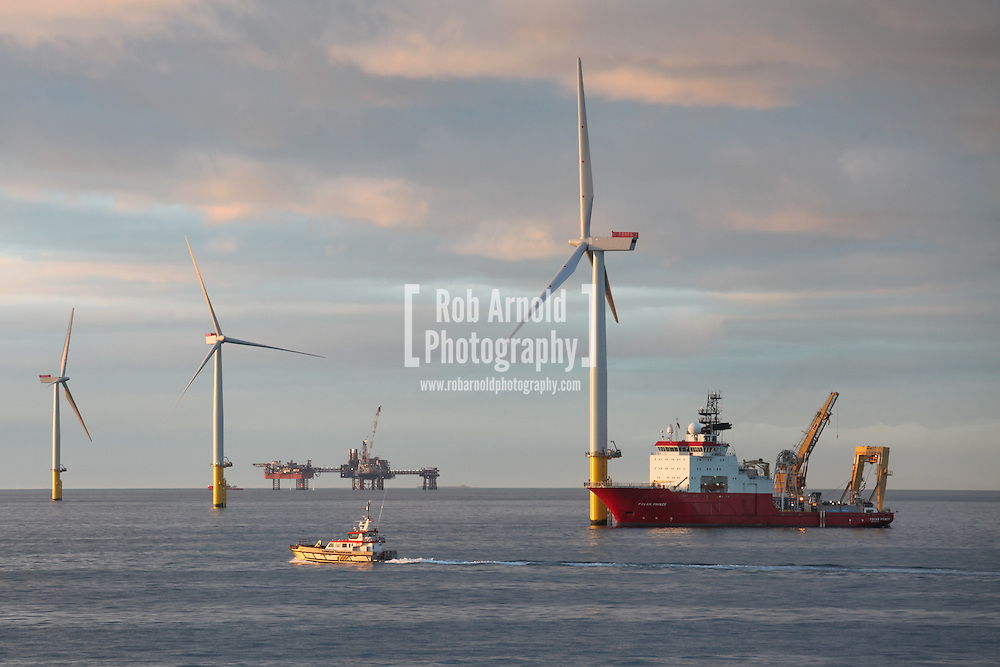 © Rob Arnold.  04/04/2014. North Wales, UK. An evening view of the cable lay vessel, Polar Prince, working on Gwynt y Môr Offshore Wind Farm off the coast of North Wales. Photo credit : Rob Arnold