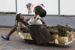 London, August 30th 2015. A couple ride in a battered coffin down a slope on Ladbroke Grove as revellers await the start of the Notting Hill Carnival.