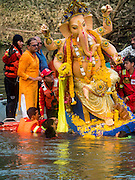 20 SEPTEMBER 2015 - SARIKA, NAKHON NAYOK, THAILAND:  The Ganesha deity is pushed overboard at the end of the Ganesh festival at Shri Utthayan Ganesha Temple in Sarika, Nakhon Nayok. Ganesh Chaturthi, also known as Vinayaka Chaturthi, is a Hindu festival dedicated to Lord Ganesh. Ganesh is the patron of arts and sciences, the deity of intellect and wisdom -- identified by his elephant head. The holiday is celebrated for 10 days. Wat Utthaya Ganesh in Nakhon Nayok province, is a Buddhist temple that venerates Ganesh, who is popular with Thai Buddhists. The temple draws both Buddhists and Hindus and celebrates the Ganesh holiday a week ahead of most other places.   PHOTO BY JACK KURTZ