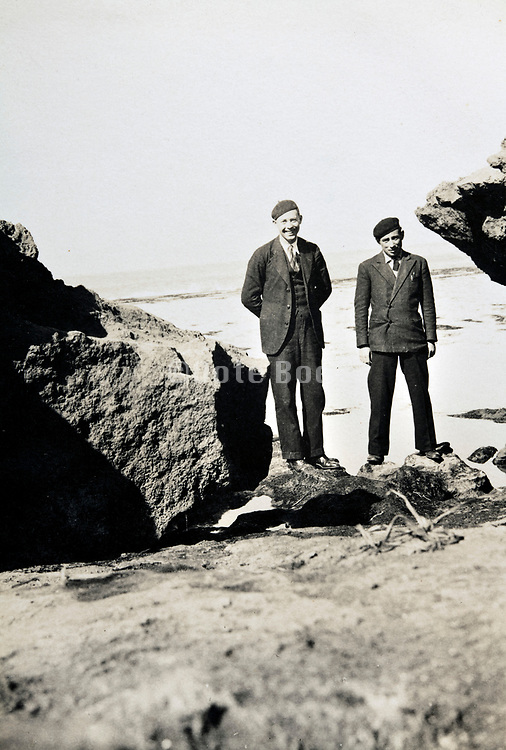 two men posing between big rocks 1930s