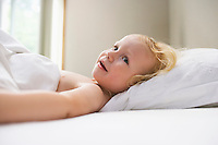 Young girl (1-2) lying in bed smiling
