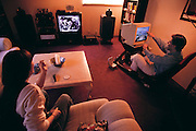 Silicon Valley, California; Jay Eisenlohr, VP of marketing for Rendition Software of Mountain View, maker of 3-D graphic chips for games. Eisenlohr in his living room playing an on-line racing game while his wife and daughter watch TV (classic old US TV shows on Nickelodeon). Model Released. (1999).