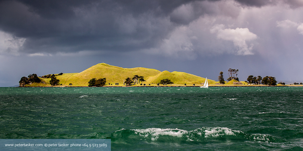 Shaft of light falls upon Browns Island during a stormy Auckland day.