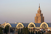 Passenger train passing the Central Market (originally built as a Zeppelin hangar) and a Stalin-Gothic highrise.