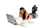 Young female student studies on the floor with headphones laptop and books