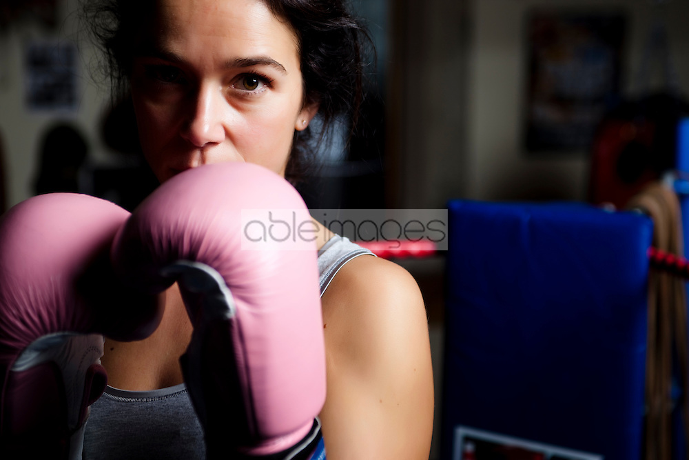 Close up of a woman wearing pink boxing gloves
