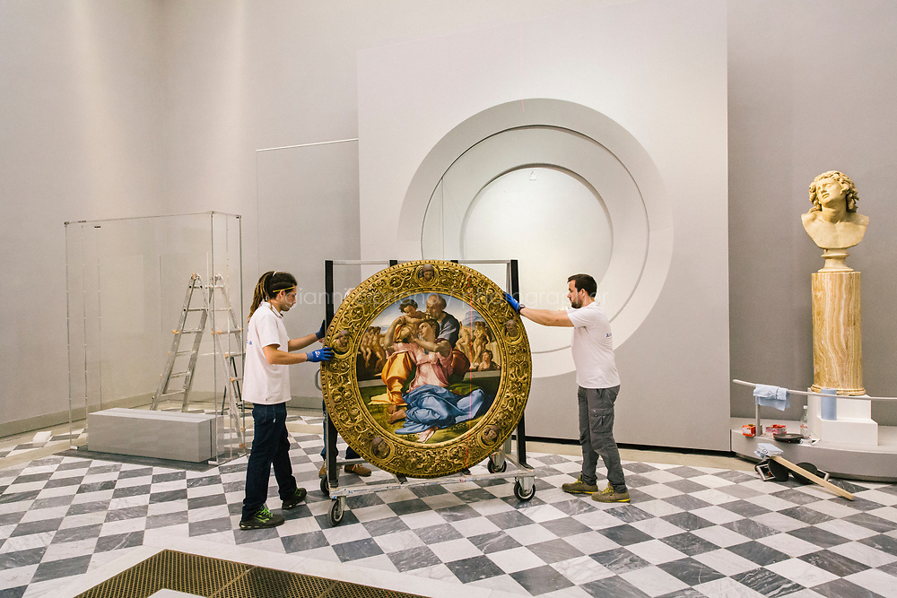 FLORENCE, ITALY - 3 JUNE 2018: Technicians are seen here at work as they position the &ldquo;Holy Family&rdquo;, also known as the Doni Tondo, that Michelangelo painted for the Doni couple around 1503-1504, to its nice at his new location in room 41at the Uffizi, in Florence, Italy, on June 3rd 2018.<br /> <br /> As of Monday June 4th 2018, Room 41 or the &ldquo;Raphael and Michelangelo room&rdquo; of the Uffizi is part of the rearrangement of the museum's collection that has<br /> been defining Uffizi Director Eike Schmidt&rsquo;s grander vision for the Florentine museum.<br /> Next month, the museum&rsquo;s Leonardo three paintings will be installed in a<br /> nearby room. Together, these artists capture &ldquo;a magic moment in the<br /> first decade of the 16th century when Florence was the cultural and<br /> artistic center of the world,&rdquo; Mr. Schmidt said. Room 41 hosts, among other paintings, the dual portraits of Agnolo Doni and his wife Maddalena Strozzi painted by Raphael round 1504-1505, and the &ldquo;Holy Family&rdquo;, that Michelangelo painted for the Doni couple a year later, known as the<br /> Doni Tondo.