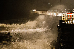 © Licensed to London News Pictures. 17/01/2018. Aberystwyth, UK.The edge of Storm Fionn's gale force winds to brings waves crashing in to the sea defences in Aberystwyth, on the Cardigan Bay coast of west wales at night  The storm has been named by the Irish Met office .Photo credit: Keith Morris/LNP