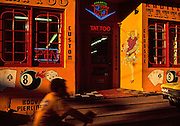 Image of a tattoo and body piercing storefront with boy on bike and yellow chevrolet outside
