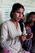 Bhawani Regmi (grey/pink), 16, attends a club meeting at the Kishuri Sachetana Child Club in their activity center in Thahuri Tole, Chhinchu, Surkhet district, Western Nepal, on 1st July 2012. Bhawani's ambition is to be a doctor. 16-year-old Bhawani Regmi (in grey/pink) who is the president of the district level child forum, 11-year-old  Sarawati Regmi (in white), and 10-year-old Ganga Regmi (in pink) are daughters of pandit (Hindu priest) Dharma Raj Regmi who is one of the 3 priests who have agreed to stop solemnizing child marriages. These Child Clubs, supported by the government, Save the Children and their local partner NGO Safer Society, advocate for child rights and against child marriages and use peer support and education to end child marriages and raise awareness. Photo by Suzanne Lee for Save The Children UK