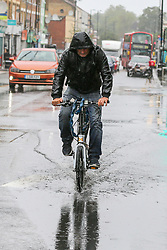 © Licensed to London News Pictures. 19/08/2020. London, UK. A cyclist rides through a puddle of rainwater in north London. According to the Met Office warmer weather with highs of 24 degrees celsius is forecasted for the rest of the week. Photo credit: Dinendra Haria/LNP