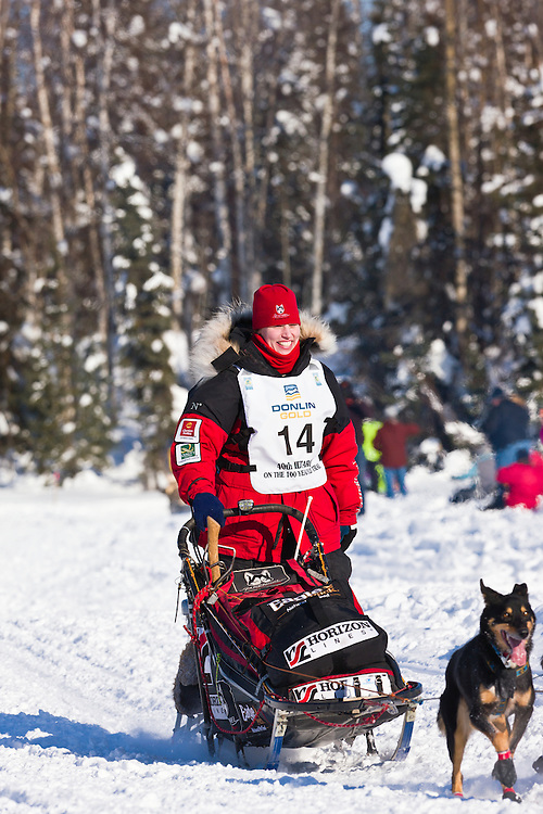 Musher Aliy Zirkle competing in the 40th Iditarod Trail Sled Dog Race on Long Lake after leaving the Willow Lake area at the restart in Southcentral Alaska. Afternoon. Winter.