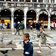 Young children run across the Piazza San Marco while chasing pigeon's. Venice, Italy. 1st May 2011. Photo Tim Clayton