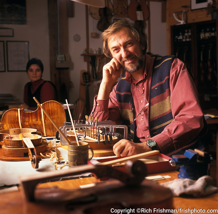 Photograph of Geza Burghardt in his luthiery shop repairing a violin in Granville Island; Vancouver, British Columbia Canada. Shown with him is his wife Tini..©Rich Frishman.