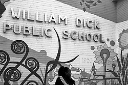 A woman sits outside as students are released early after a stabbing occurred   inside William Dick Public School, in the Strawberry Mansion neighborhood.